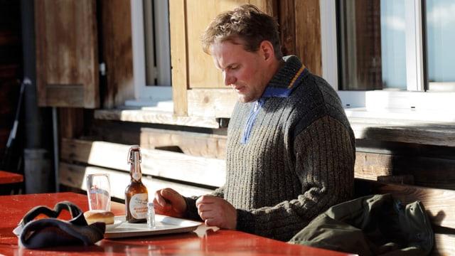Ein Mann sitzt am draussen an einem Restauranttisch vor einer Flasche Bier.