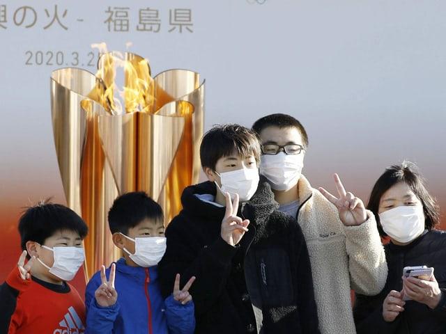 Menschen posieren vor der olympischen Flamme in Tokio.