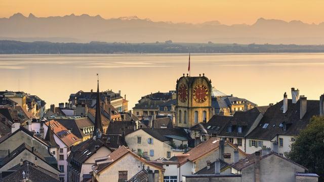 Die Stadt Neuchâtel, dahinter der See im Abendrot.