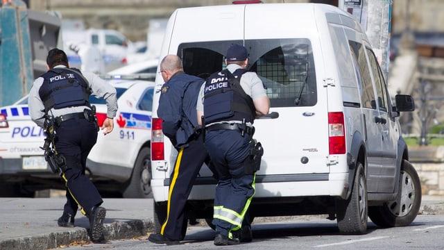 Kanadische Polizisten verstecken sich hinter einem Einsatzfahrzeug im Parlamentsviertel von Ottawa