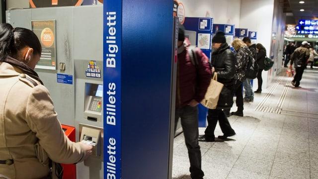 Personen kaufen ihr Bahnbillett an einem Automaten