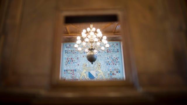 Durch ein Fenster in einer Holztür sieht man einen Kronleuchter, dahinter eine blaue Wand mit dem Zürcher WAppen.