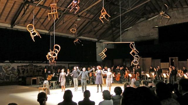 Schauspieler beziehen Applaus, von der Decke hangen Stühle.