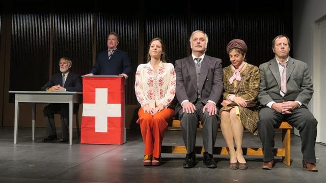 Szene in einem Landtheater: Ein Politiker steht an einem Rednerpult mit Schweizerfahne, daneben sitzen vier Leute auf einer Bank.