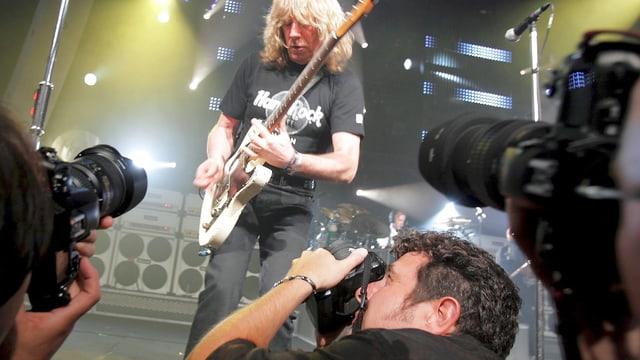 Ein Bassist wird während eines Konzertes von drei Fotografen porträtiert.