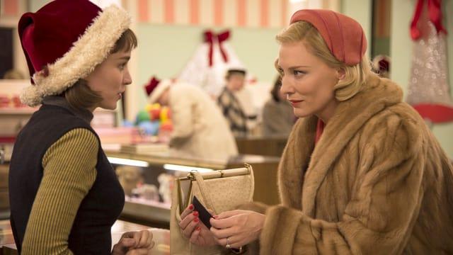 Ein Warenhaus: Eine Dame im Pelzmantel liebäugelt mit einer Verkäuferin mit Nikolausmütze über den Ladentisch hinweg.