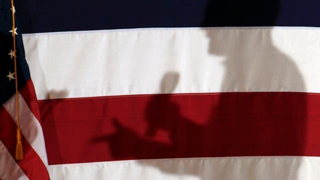 Der Schattenwurf eines Mannes mit Mikrofon hinter einer US-Flagge.