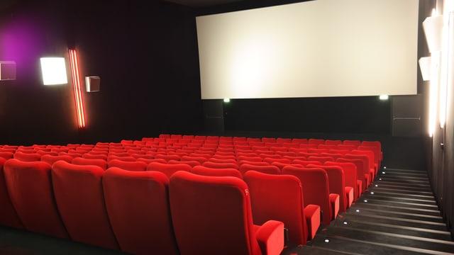 Ein Kinosaal mit roten Sesseln und Leinwand
