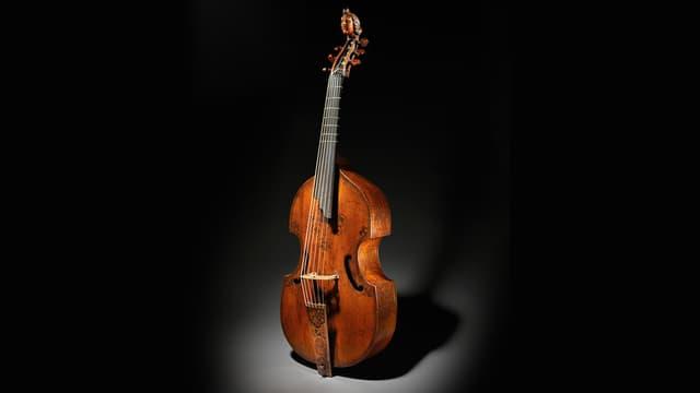 Eine Viola da gamba vor schwarzem Hintergrund.