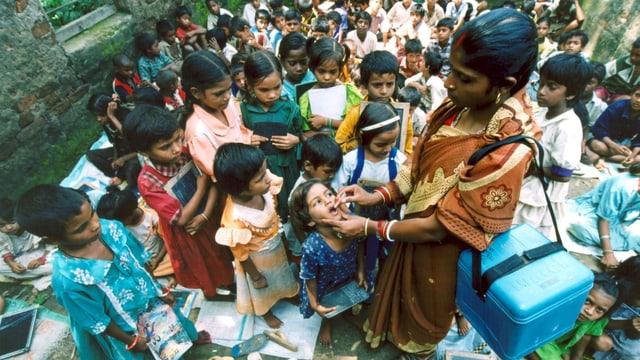 Eine Helferin umringt von dutzenden Kindern verteilt Schluckimpfungen.