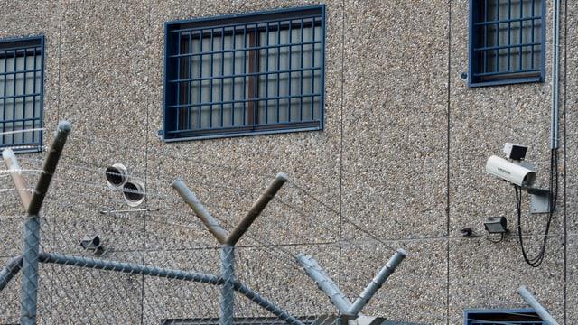 Fassade eines Gefängnisses mit Stacheldraht und vergitterten Fenstern.