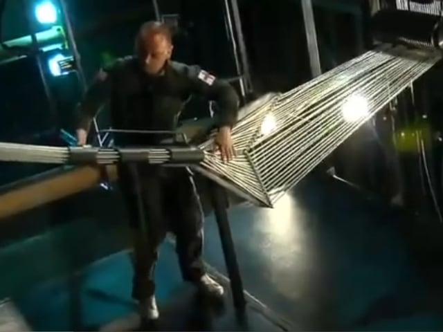Mark Bell steht an einer seltsamen Maschine, durch die dicke Seile laufen. Er spielt sie wie einen Bass.