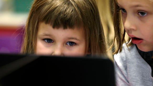 zwei Mädchen sitzen vor dem Computer