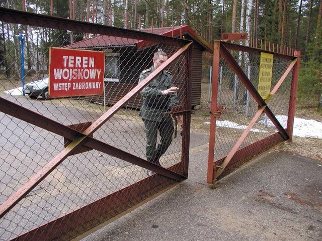 Soldat schliesst ein Gittertor auf einer Strasse