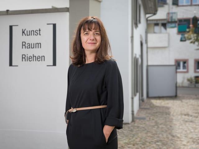 Eine Frau im schwarzen Kleid steht vor einem Gebäude mit der Schrift «Kunst Raum Riehen».