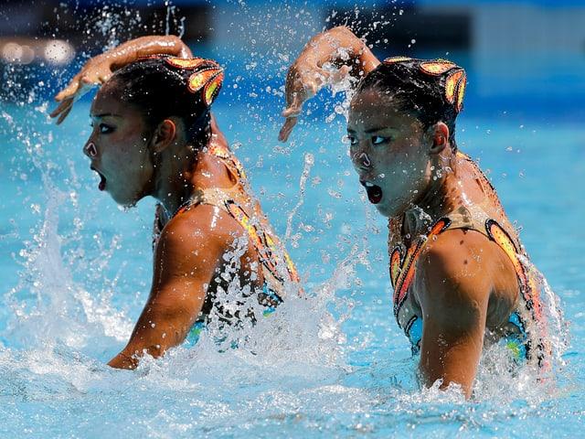 Schwimmerinnen mit Hand vor dem Gesicht.