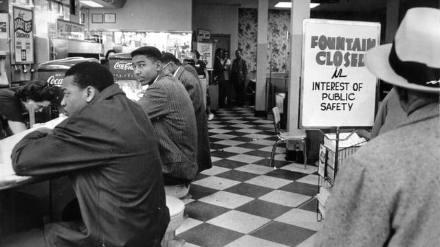 Einige afro-amerikaner sitzen an einem Restaurant-Tresen, der nur für Weisse vorgesehen ist.