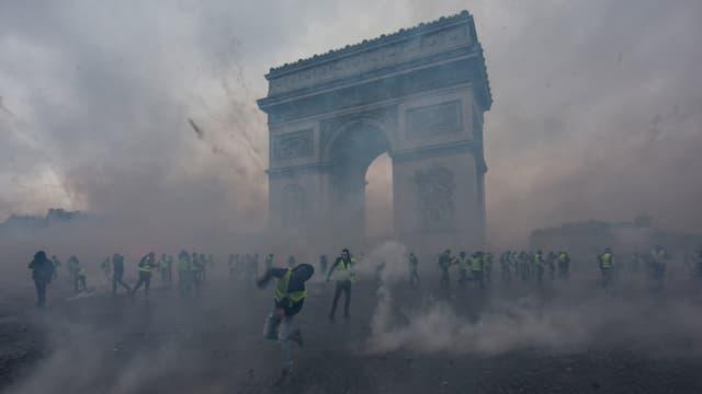 Gilets Jaunes vor dem Arc de Triomphe umgeben von Rauch