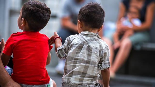 Zwei Kinder, fotografiert von hinten.