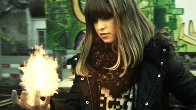 Mädchen mit Flamme in der offenen Hand.