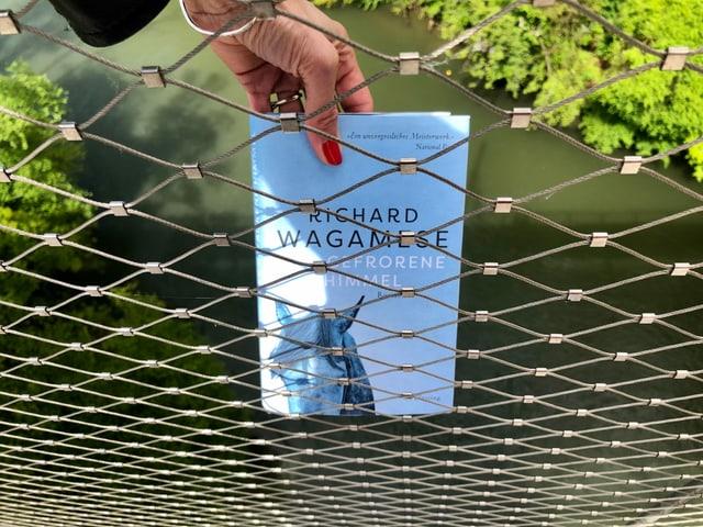 Annette König hält den Roman «Der gefrorene Himmel» von Richard Wagamese hinter ein Gitter. Im Hintergrund ist ein Fluss sichtbar.