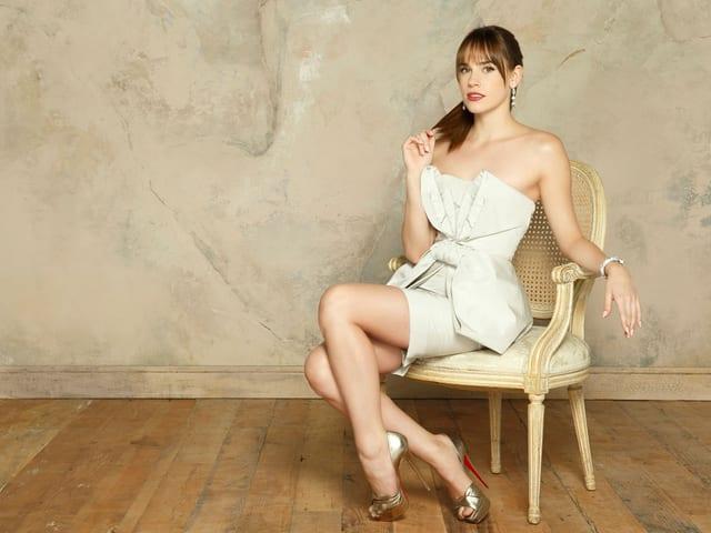 Eine Frau in weissem Abendkleid sitzt auf einem Stuhl.