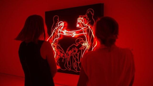 Besuchen schauen sich eine Lichtinstallation von Bruce Nauman an. Sie ist rot und zeigt ein Paar beim Sex.