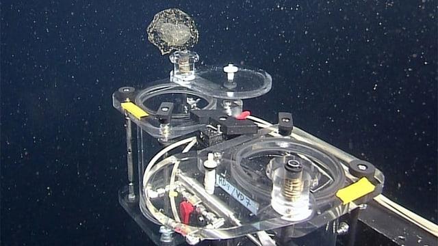 Ein Gebilde aus Metall, Plastik und Kabeln umgeben von dunklem Wasser.