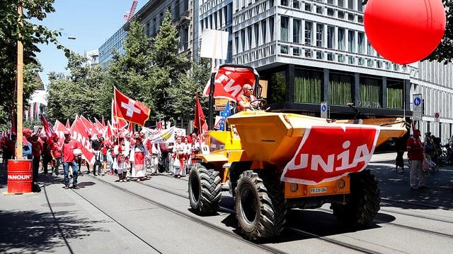 Demonstrationszug in der Zürcher Innenstadt, angeführt von einem Baufahrzeug.