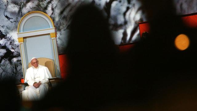 Zwischen dunklen Menschensihouetten sitzt der Papst auf einem Sessel.