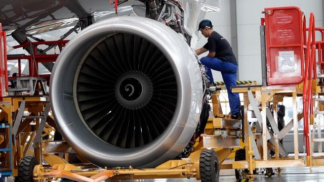 Ein Angestellter in einer Airbus-Fabrikationshalle arbeitet an der Fertigstellung eines Triebwerks.