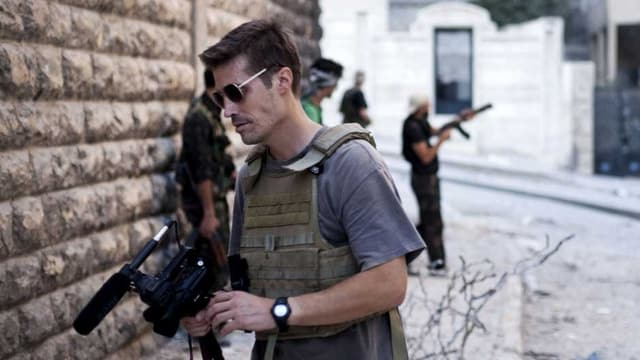 Kriegsreporter Foley mit einer TV-Kamera im Vordergrund – im Hintergrund ein Rebell mit einer Maschinenpistole.