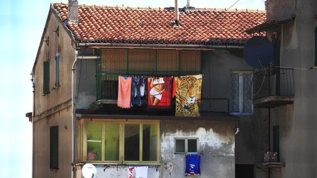Heruntergekommenes Haus mit Wäscheleine am Balkon.