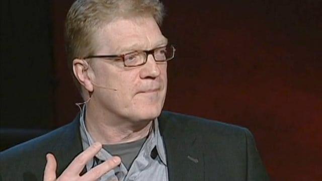 Ein Mann mit Brille hält einen Vortrag.