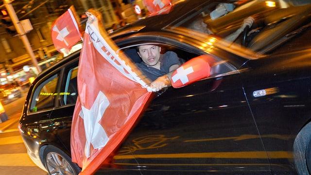 Ein Fussballfan hält in Zürich eine Schweizer Flagge aus einem fahrenden Auto