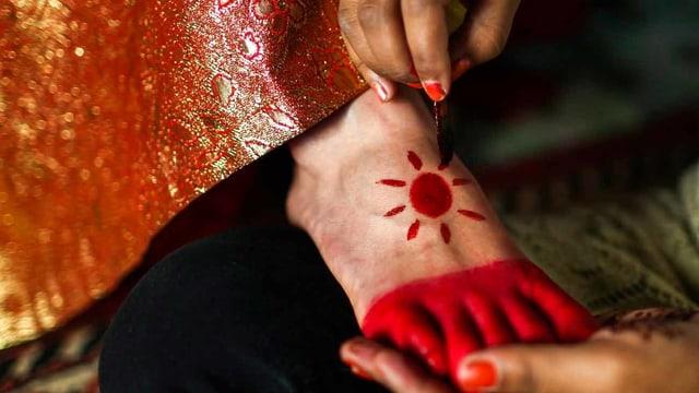 Füsse werden angemalt - die Zehen rot und auf dem Fussrücken eine Sonne.