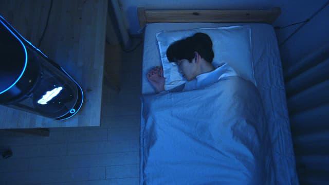 Ein junger Mann schläft auf seinem Bett, neben ihm ist ein Hologramm unter einer Glaskuppel