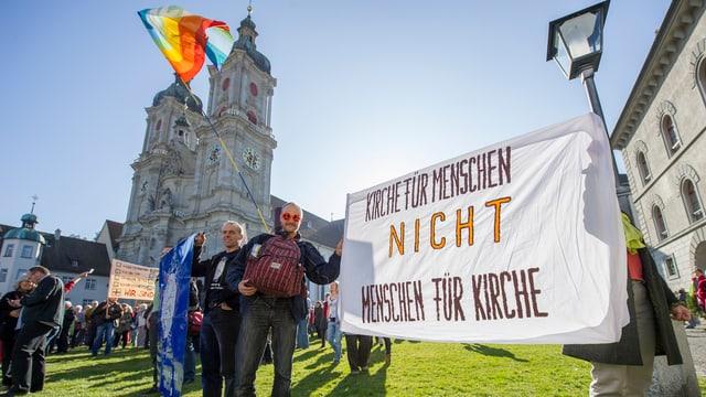 """Menschen stehen vor einer Kirche und halten ein Transparent mit der Aufschrift """"Kirche für Menschen und nicht Menschen für Kirche""""."""