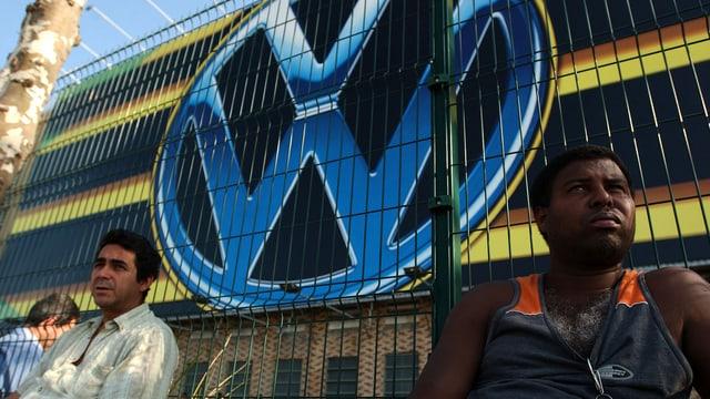 Arbeiter vor einem Zaun, dahinter das VW-Emblem.