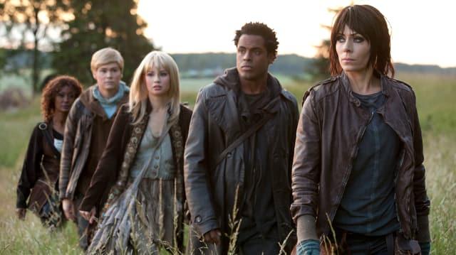 Fünf Hubots, drei Frauen und zwei Männer laufen hintereinander durch ein Feld.