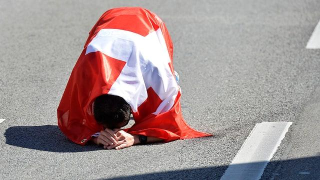 Viktor Röthlin, eingehüllt in die Schweizer Fahne, kniet am Boden.