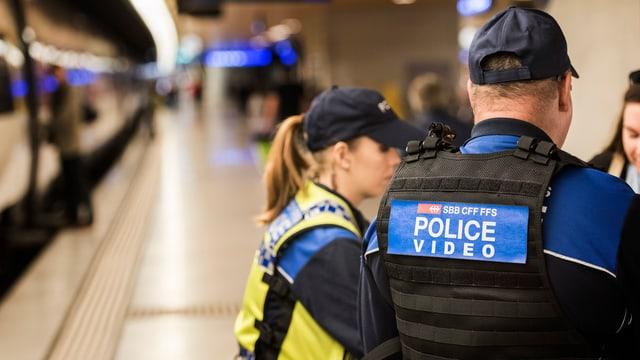 Zwei Polizisten neben einem Zug.