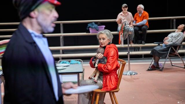Bühnenszene: Frau hält Puppe im Arm, Man spricht im Vordergrund