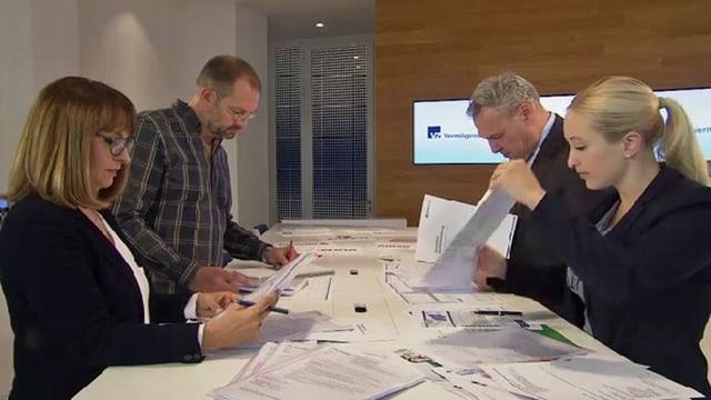 Vier Personen stehen an einem Tisch und kontrollieren Dokumente.