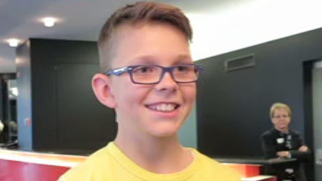 Ein Junge mit Brille und gelbem Pulli