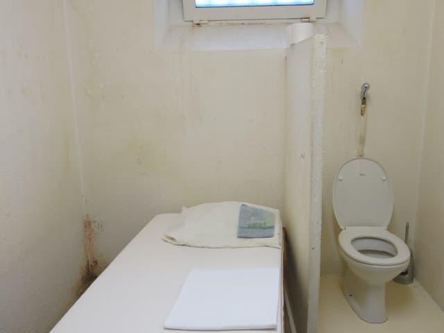Eine Zelle mit einem Bett und einem WC.