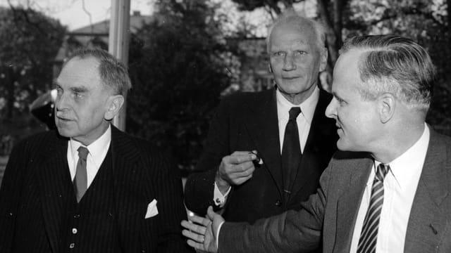 Otto Hahn, Walter Gerlach und Carl Friedrich, alle in Anzug und Krawatte, eilig an der Kamera vorbeigehend.
