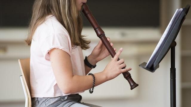 scolara emprenda da sunar flauta.