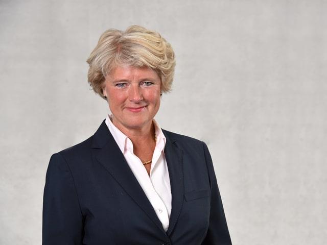 Eine Frau mit blonden, eher kürzeren haaren lächelt in die Kamera. Sie steht vor einer grauen Betonwand und trägt eine weisse Bluse und einen schwarzen Blazer.