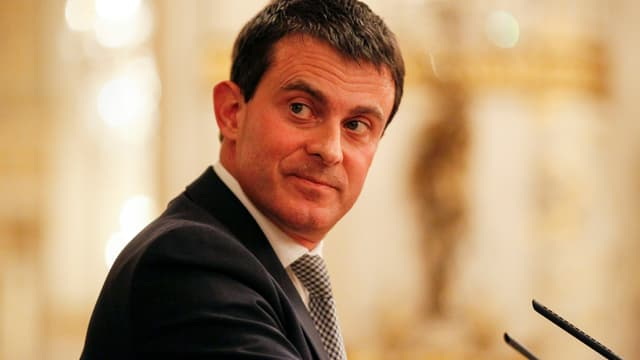 Valls blickt vor einem Mikrofon rechts über die Schulter zurück.